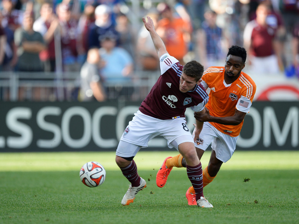 . Colorado Rapids midfielder Dillon Powers (8) gets pulled by the arm by Houston Dynamo defender Warren Creavalle (5) as he tries to gain control of the ball during the first half June 1, 2014 at Dick\'s Sporting Goods Park. (Photo by John Leyba/The Denver Post)