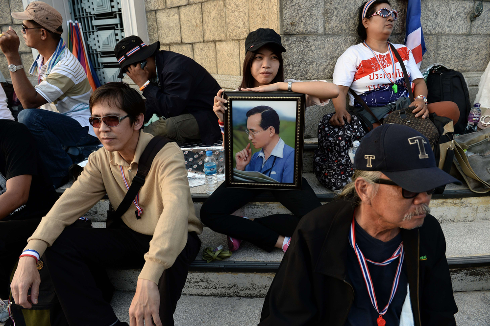 """. A Thai anti-government protester holds a portrait of King Bhumibol Adulyadej as protesters occupy Victory Monument in downtown Bangkok on January 13, 2014.  Tens of thousands of Thai opposition protesters occupied major streets in central Bangkok on January 13 in an attempted \""""shutdown\"""" of the capital, escalating a campaign to unseat the embattled premier. (CHRISTOPHE ARCHAMBAULT/AFP/Getty Images)"""