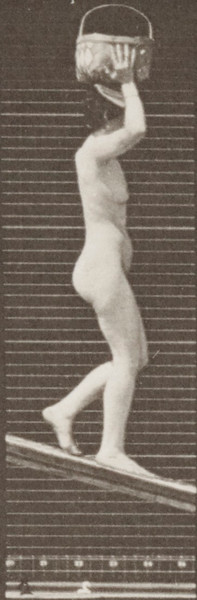 Nude woman descending an incline with a basket on head