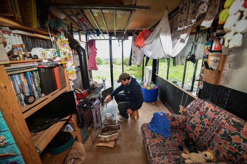 Newport, Pembrokeshire, Saturday, 8th June 2019 The home owned and built by Matthew and Charis Watkinson in Newport, Pembrokeshire, which is zero carbon and fully self-sustaining.   Matthew fills the log burning stove in the living room of the home.