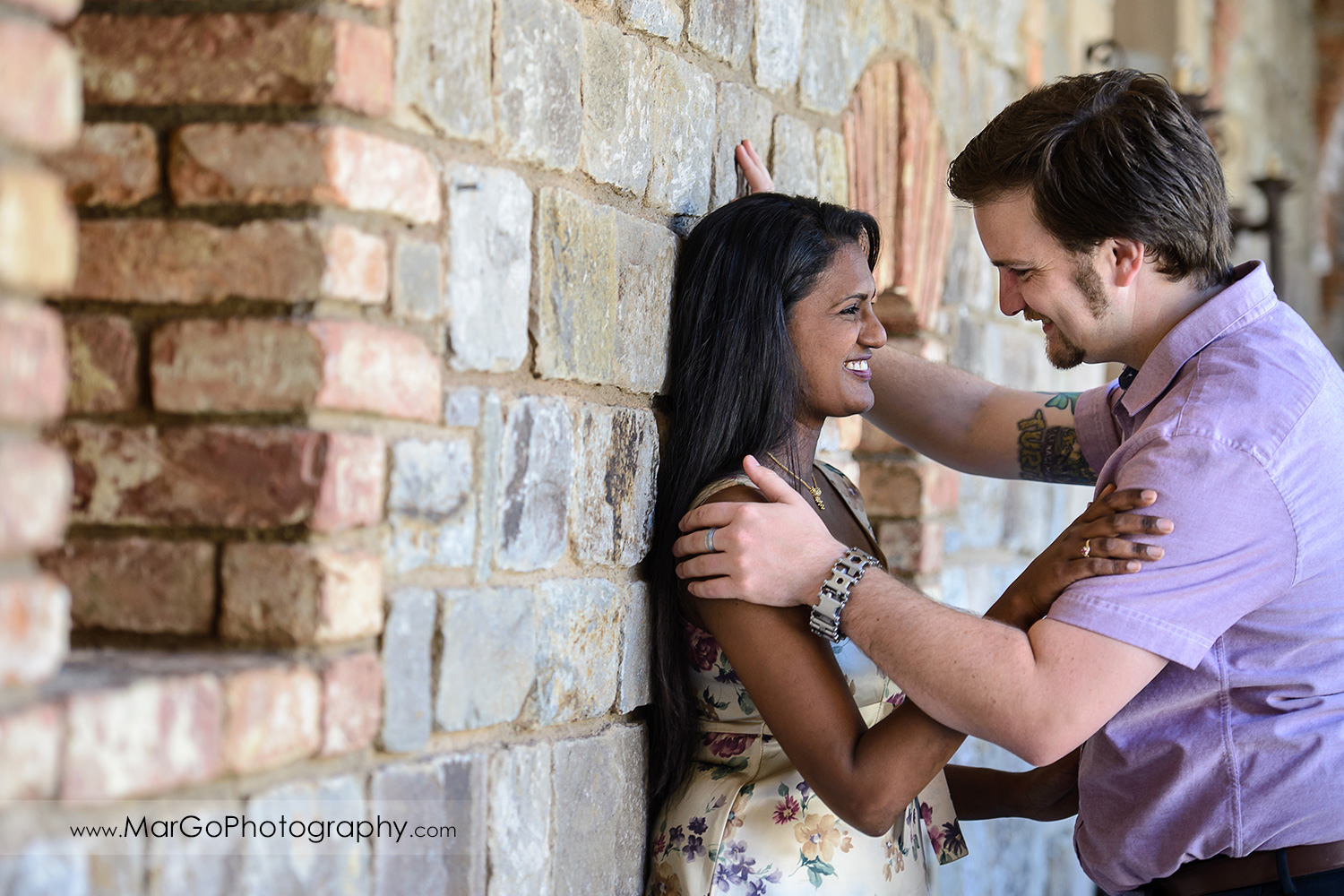 man in pink shirt and Indian woman in flower dress leaning against the brick wall and laughing during engagement session at Castello di Amorosa in Calistoga
