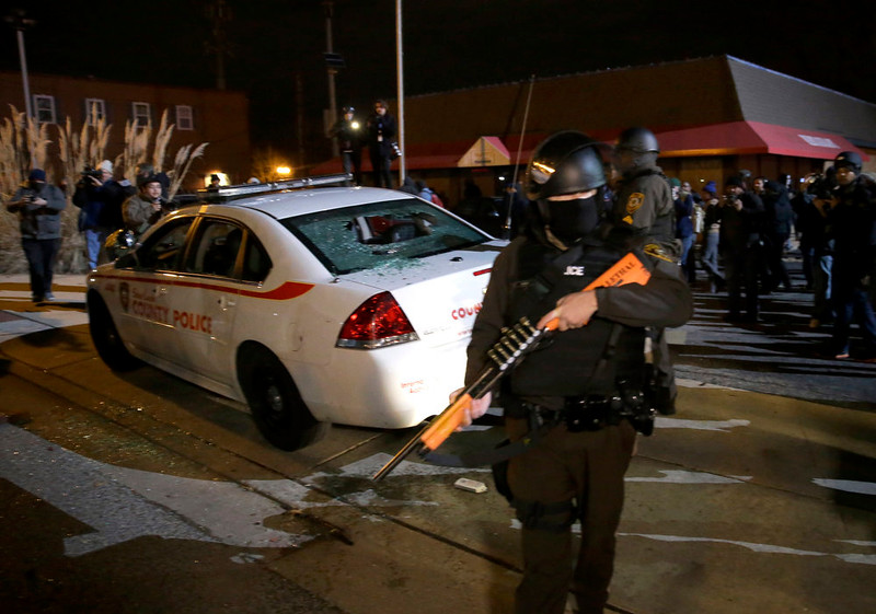 . An armed police officer guards the area after a group of protesters vandalize a police cruiser after the announcement of the grand jury decision not to indict police officer Darren Wilson in the fatal shooting of Michael Brown, an unarmed black 18-year-old, Monday, Nov. 24, 2014, in Ferguson, Mo. (AP Photo/David Goldman)