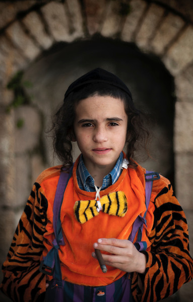 """Children are sometimes allowed to smoke during the Purim celebrations under the excuse of having fun.  For more on smoking and drinking during Purim please visit """"the people of Mea Shaerim"""" under the """"meet the people"""" gallery.  Mea Shearim, Jerusalem, Israel, 2012."""
