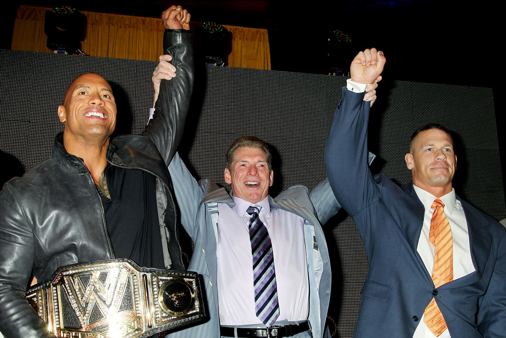 Description of . This image released by Starpix shows actor and WWE star Dwayne Johnson, better known as The Rock, left, with Vince McMahon, and WWE star John Cena, right, at a news conference at Radio City Music Hall in New York on Thursday, April 4, 2013.  Johnson and Cena will face off in the ring at Wrestlemania 29 on Sunday, April 7, at at MetLife Stadium in East Rutherford, N.J.  (AP Photo/Starpix, Dave Allocca)