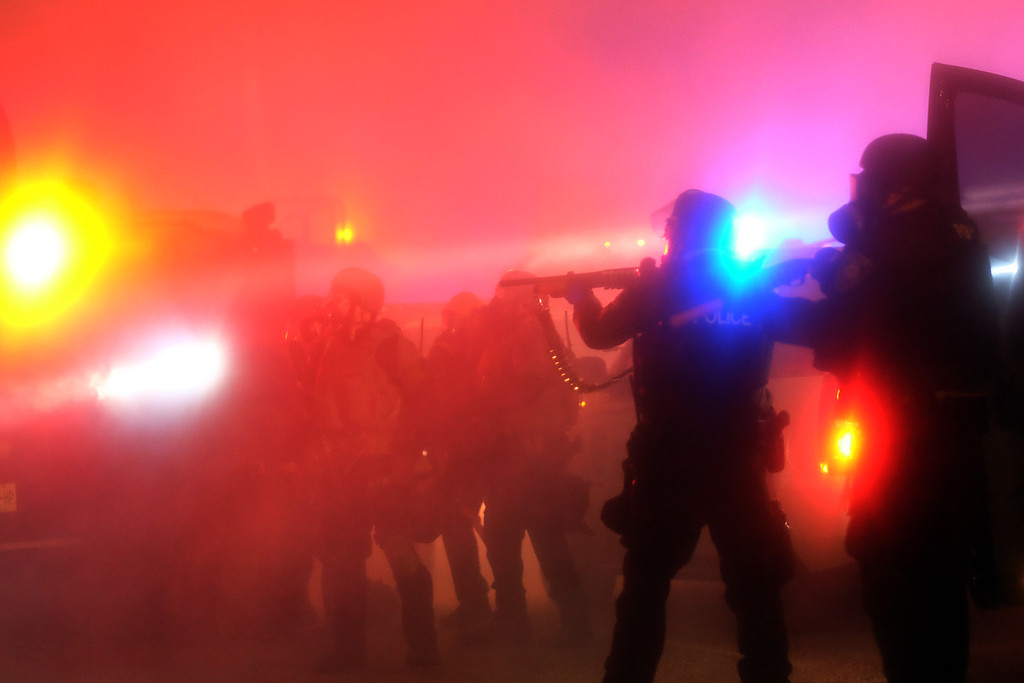 . Police are engulfed in tear gas during clashes with protesters  following the grand jury decision in the death 18-year-old Michael Brown in Ferguson, Missouri, on November 24, 2014.  Violent protests and looting erupted in the US town of Ferguson after a grand jury chose not to press charges against a white officer who shot dead the black teen.  US President Barack Obama and the family of late 18-year-old Michael Brown separately appealed for calm after a prosecutor said a grand jury had found the policeman acted in self-defense. AFP PHOTO/Jewel SAMAD/AFP/Getty Images