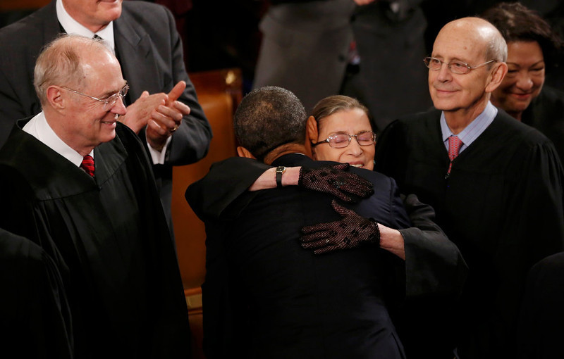 . U.S. Supreme Court Justice Ruth Bader Ginsburg hugs President Barack Obama as fellow Supreme Court Justices Anthony Kennedy (L) and Stephen Breyer (R) look on as the President arrives to deliver his State of the Union speech on Capitol Hill in Washington, February 12, 2013.  REUTERS/Jason Reed