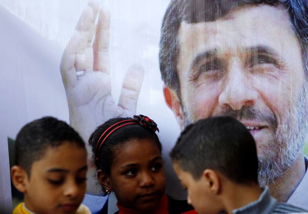 Description of . Children stand in front of a poster of Iran's President Mahmoud Ahmadinejad in front of the Al-Hussein mosque, named after Prophet Mohammed's grandson Hussein ibn Ali, before Ahmadinejad's visit to the mosque in old Cairo February 5, 2013. Ahmadinejad was both kissed and scolded on Tuesday when he began the first visit to Egypt by an Iranian president since Tehran's 1979 Islamic revolution. The trip was meant to underline a thaw in relations since Egyptians elected an Islamist head of state, President Mohamed Mursi, last June. But it also highlighted deep theological and geopolitical differences. REUTERS/Amr Abdallah Dalsh