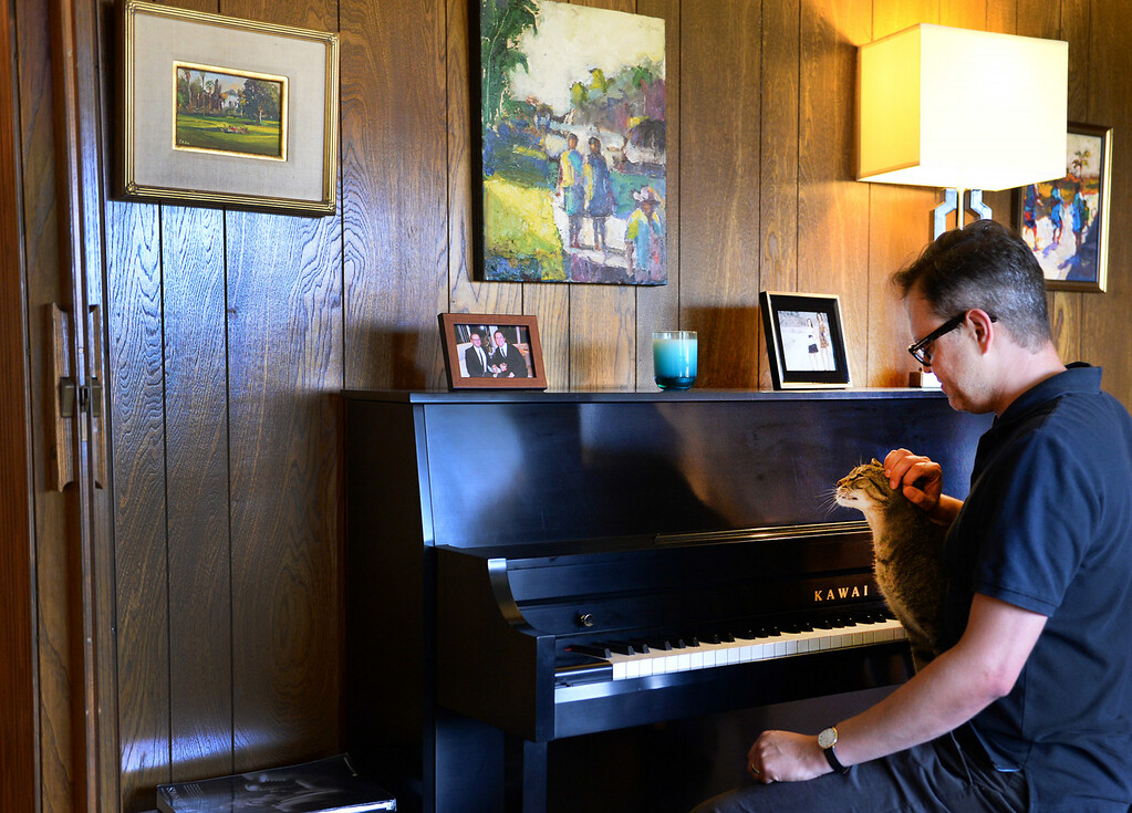 . Redlands resident Nathan Gonzales sits at the piano with Buster, one of two of his cats, on Thursday, July 10, 2014 in Redlands, Ca. Gonzales\' home was added to the city�s historic register list and is the second post-World War II era building added to it. (Photo by Micah Escamilla/Redlands Daily Facts)
