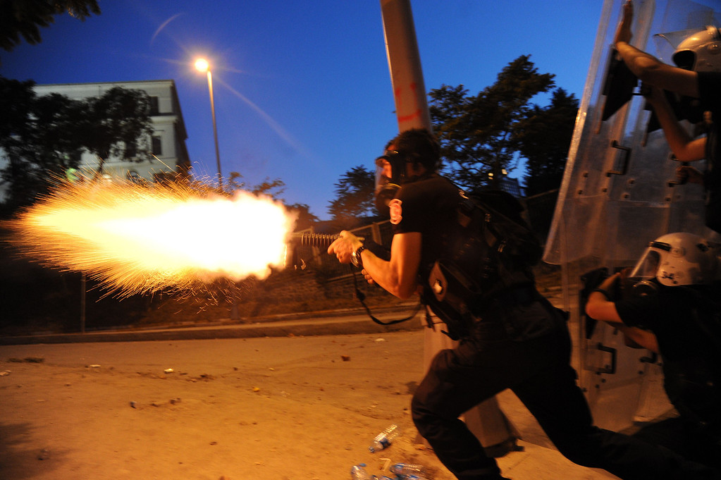 . A Turkish riot police officer fires tear gas during clashes with protestors between Taksim and Besiktas in Istanbul on June 3, 2013 during a demonstration against the demolition of the park.   BULENT KILIC/AFP/Getty Images