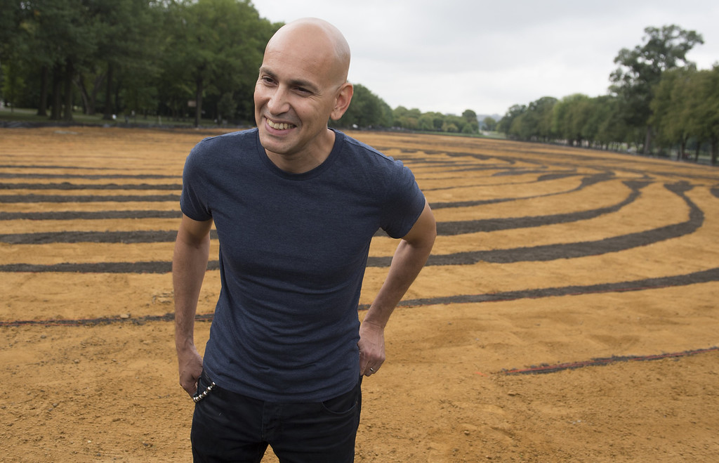 """. Cuban American artist Jorge Rodriguez-Gerada talks about his landscape portrait, \""""Out of Many, One\"""" on the National Mall in Washington, DC, October 1, 2014. SAUL LOEB/AFP/Getty Images"""