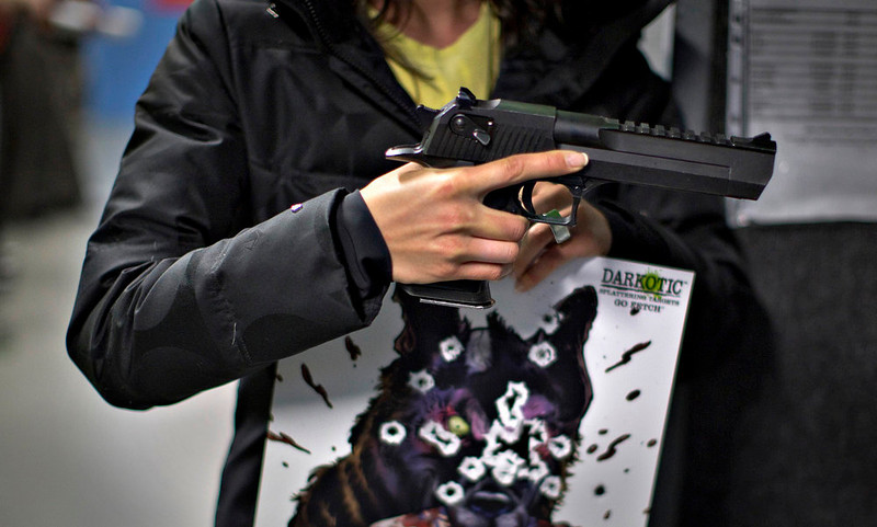 . A woman holds a .50AE Desert Eagle and her target while visiting the DVC Indoor Shooting Centre in Port Coquitlam, British Columbia March 22, 2013. The DVC is the only indoor shooting centre in the province that rents firearms to the public without a license. The centre has several kinds of pistols from 38 specials 44 magnums. Canada has very strict laws controlling the use of handguns and violent crime is relatively rare. Picture taken March 22, 2013.  REUTERS/Andy Clark   ATTENTION EDITORS: PICTURE 21 OF 24 FOR PACKAGE \'GUN CULTURE - CANADA\'  SEARCH \'CANADA GUN\' FOR ALL IMAGES
