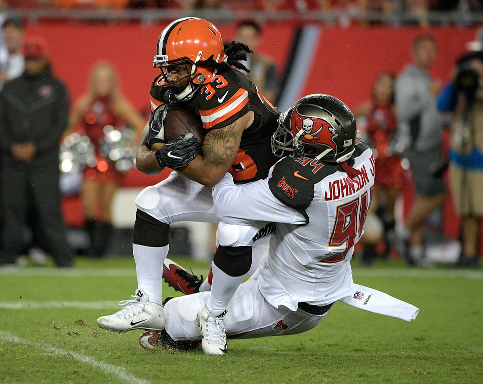 . Cleveland Browns running back Terrence Magee (33) is stopped by Tampa Bay Buccaneers defensive end George Johnson Jr., (94) during the third quarter of an NFL preseason football game Saturday, Aug. 26, 2017, in Tampa, Fla. (AP Photo/Phelan Ebenhack)