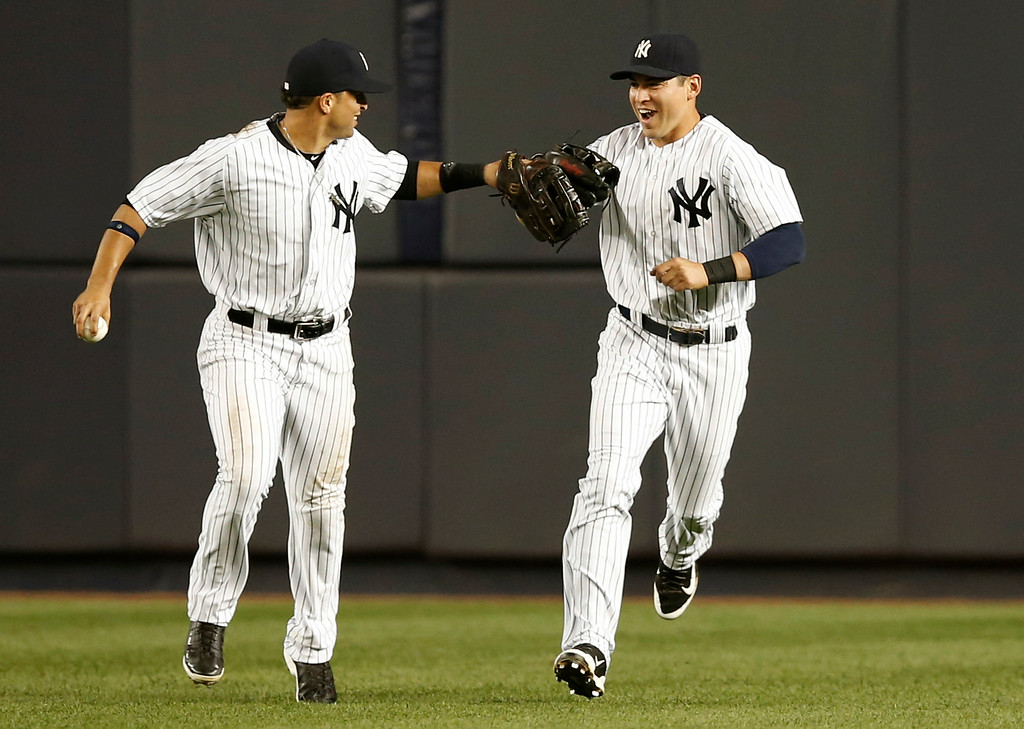 . New York Yankees right fielder Martin Prado (14) congratulates Yankees center fielder Jacoby Ellsbury (22) after Ellsbury caught Detroit Tigers J.D. Martinez\'s sixth-inning fly out at the bullpen wall in a baseball game at Yankee Stadium in New York, Wednesday, Aug. 6, 2014.  (AP Photo/Kathy Willens)