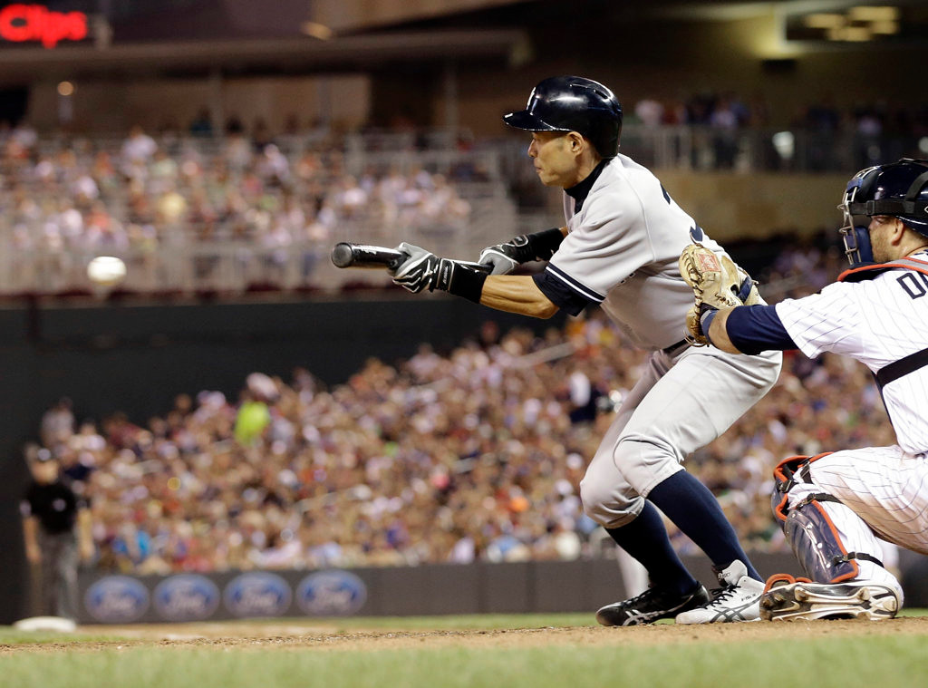 . New York Yankees pinch hitter Ichiro Suzuki lays down a bunt off Minnesota Twins pitcher Jared Burton in the eighth inning. (AP Photo/Jim Mone)