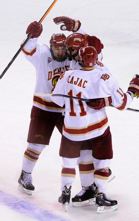 . DENVER, CO. - OCTOBER 12: Denver defenseman David Makowski (10) celebrated his first goal of the season with teammates in the second period. The University of Denver hockey team hosted Merrimack at Magness Arena, Saturday night, October 12, 2013. Photo By Karl Gehring/The Denver Post