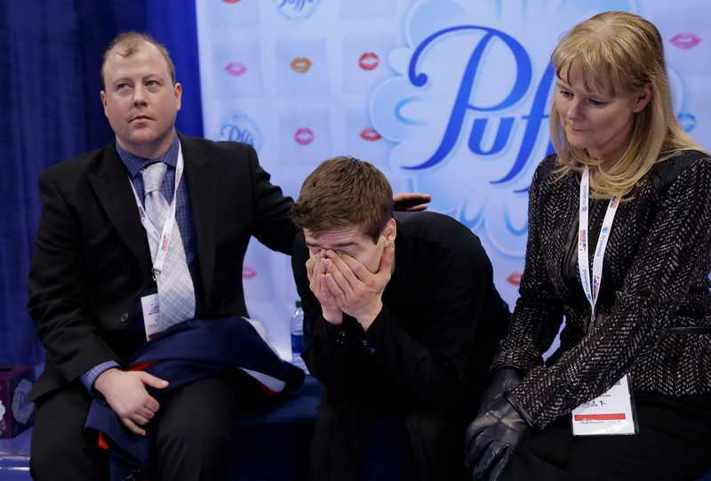. Richard Dornbush, center, reacts as he learns his scores as his coaches Justin Dillon, left, and Tammy Gambill, right, look on after competing in the men\'s free skate at the U.S. Figure Skating Championships Sunday, Jan. 12, 2014 in Boston. (AP Photo/Steven Senne)