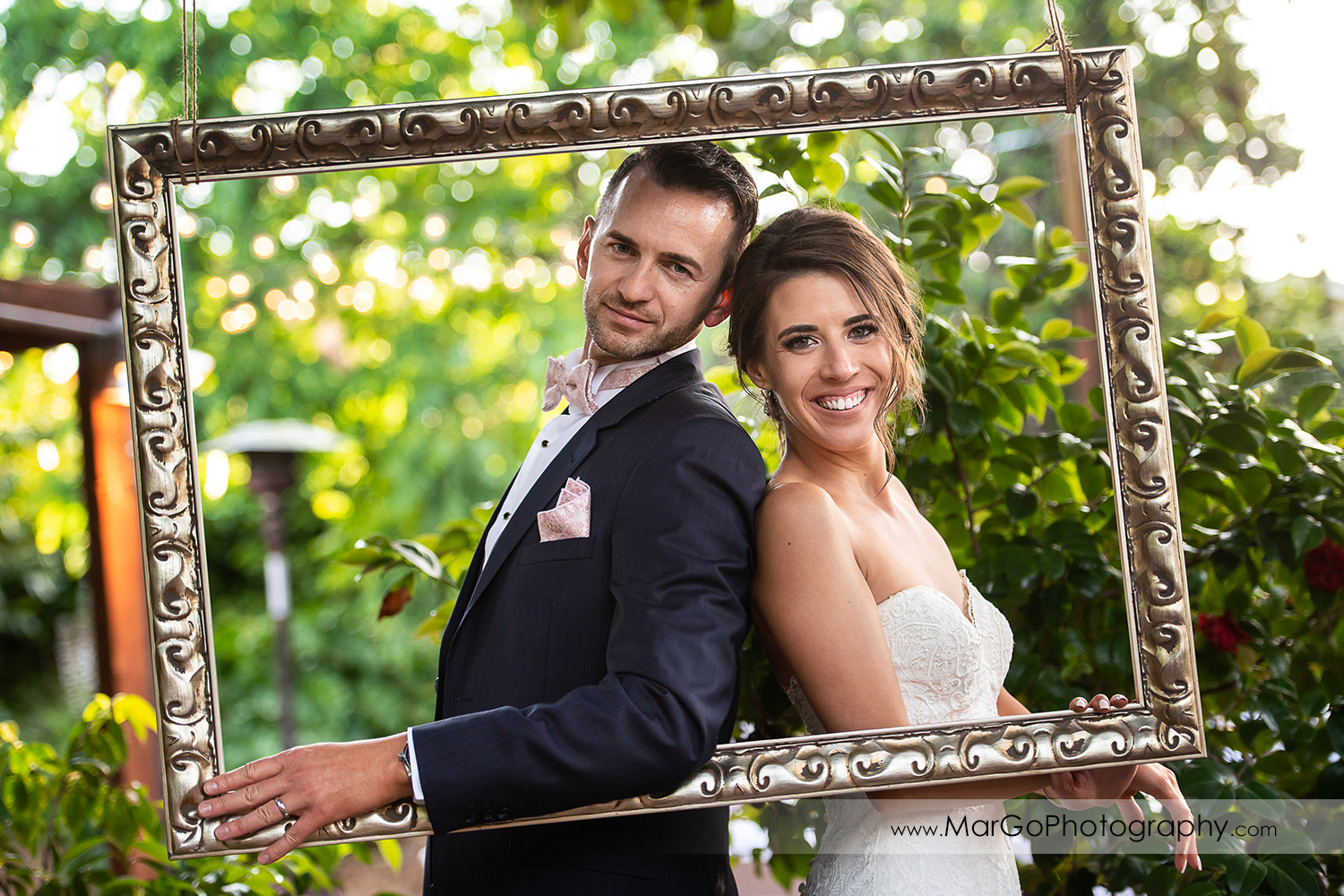 portrait of bride and groom in golden frame at wedding reception at San Pablo Rockefeller Lodge