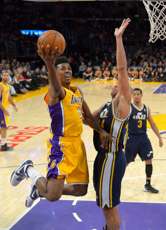 . Los Angeles Lakers forward Nick Young, left, puts up a shot as Utah Jazz forward Richard Jefferson defends during the first half of an NBA basketball game, Friday, Jan. 3, 2014, in Los Angeles. (AP Photo/Mark J. Terrill)