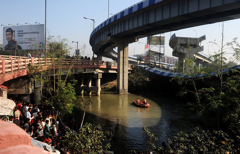. Indian onlookers watch as rescue personnel search waters near the collapsed portion of the flyover in Kolkata on March 3, 2013. A huge portion of a flyover on the eastern side of the Indian metropolis collapsed leaving three persons injured, the flyover connects the airport with Eastern Metropolitan Bypass and the eastern and southern suburbs.   As the debris fell into a canal running below the flyover, it took down a truck the driver and two others were rescued from the canal by fire-brigade personnel and locals.   DIBYANGSHU SARKAR/AFP/Getty Images