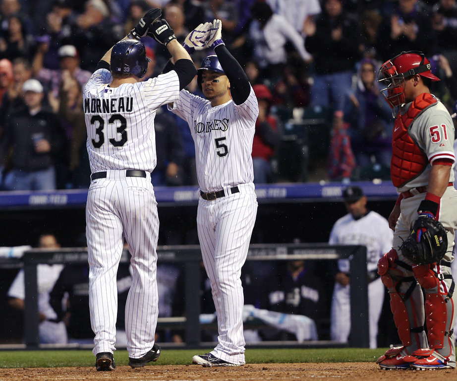 . Colorado Rockies\' Justin Morneau, left, is congratulated for his two-run home run by teammate Carlos Gonzalez, center, as Philadelphia Phillies catcher Carlos Ruiz looks on in the fourth inning of a baseball game in Denver on Saturday, April 19, 2014. (AP Photo/David Zalubowski)