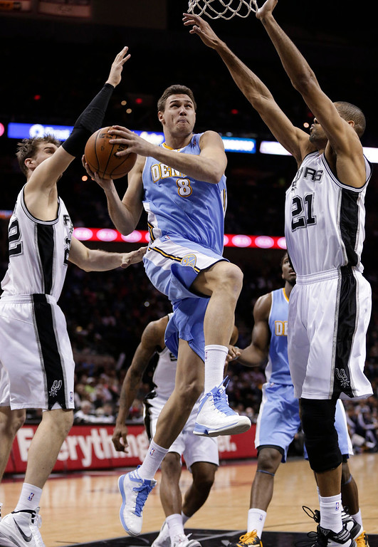 . Denver Nuggets\' Danilo Gallinari (8) drives to the basket between San Antonio Spurs\'  Tiago Splitter, left, of Brazil, and Tim Duncan (21) during the second half of an NBA basketball game, Wednesday, March 27, 2013, in San Antonio. San Antonio won 100-99. (AP Photo/Eric Gay)
