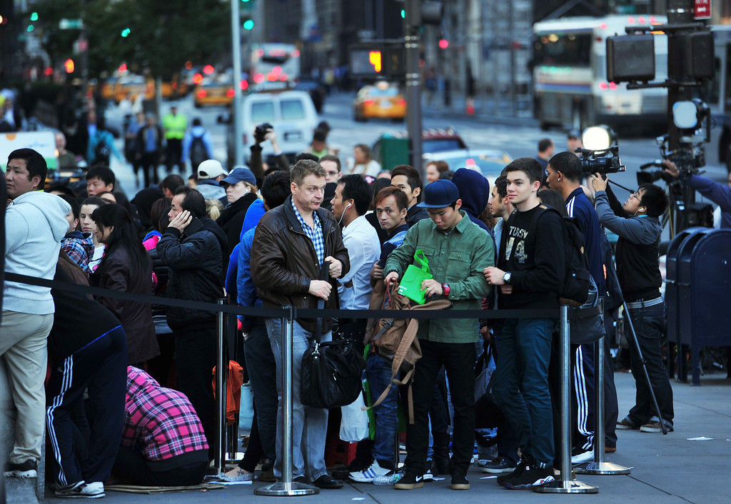 . People waiting to buy the Apple iPhone 5 in line at the Apple Store on Fifth Avenue September 20, 2013 in New York. Some people waited as long as fifteen days in line outside the store to be the first to buy the phone. AFP PHOTO/Stan HONDA/AFP/Getty Images