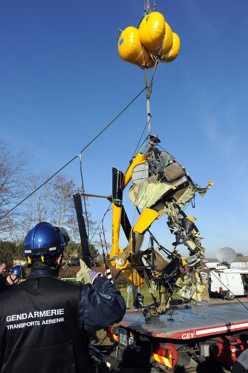 . Gendarmes load wreckages of the crashed Robinson R44 helicopter on a truck in Lugon-et-l\'Ile-du-Carnay, southwestern France, on December 23, 2013 after they lifted it from the Dordogne river bed. AFP PHOTO / MEHDI FEDOUACH/AFP/Getty Images