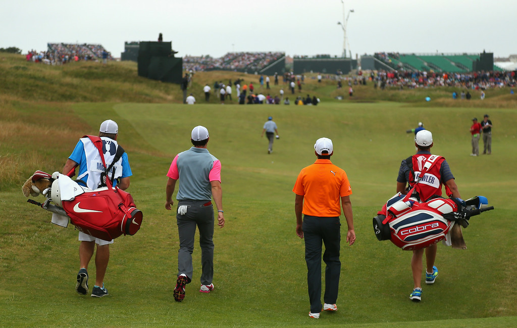 . Rory McIlroy of Northern Ireland (centre left) and Rickie Fowler of the United States (centre right) walk off the 11th tee with their caddies during the final round of The 143rd Open Championship at Royal Liverpool on July 20, 2014 in Hoylake, England.  (Photo by Mike Ehrmann/Getty Images)