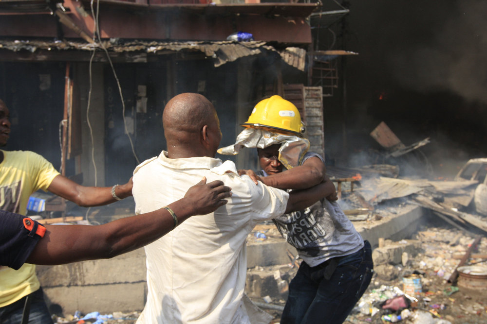 Description of . Men fight over a fire helmet as a fire burns on Lagos Island in Lagos, Nigeria, on Wednesday, Dec. 26, 2012. An explosion ripped through a warehouse Wednesday where witnesses say fireworks were  stored in Nigeria\'s largest city, sparking a fire. It wasn\'t immediately clear if anyone was injured in the blast that firefighters and locals struggled to contain. (AP Photo/Jon Gambrell)