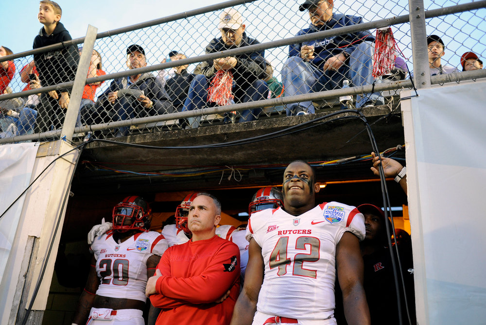 . Rutgers head coach Kyle Flood, bottom center, stands with linebackers Khaseem Greene, left, and Steve Beauharnais, right, as they prepare to run out of the tunnel and onto the field at the start of an NCAA college football Russell Athletic Bowl game against Virginia Tech, Friday, Dec. 28, 2012, in Orlando, Fla. (AP Photo/Brian Blanco)