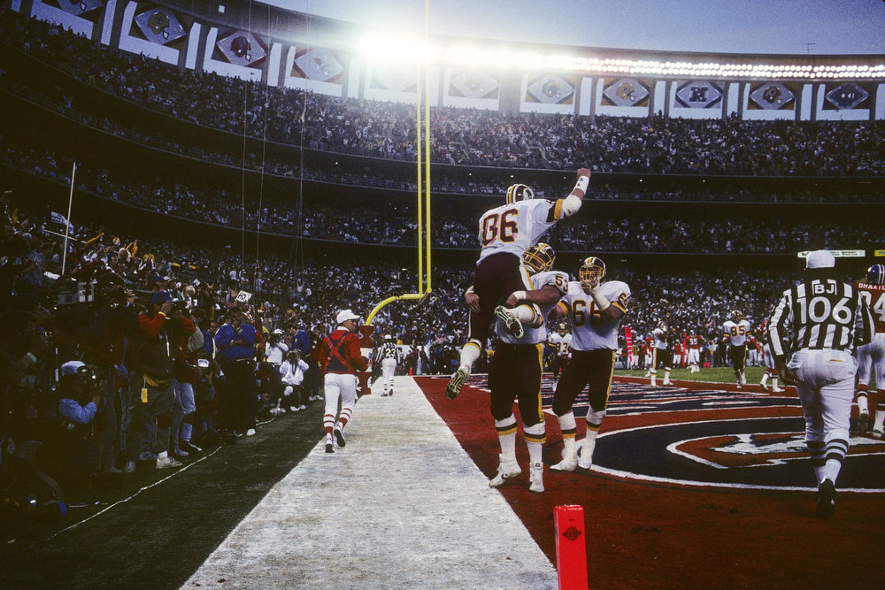 Description of . Tight end Clint Didier #86 (T) of the Washington Redskins celebrates with teammate Jeff Bostic #53 (B) after scoring a touchdown during Super Bowl XXII against the Denver Broncos at Jack Murphy Stadium on January 31, 1988 in San Diego, California.  The Redskins won 42-10.  (Photo by George Rose/Getty Images)