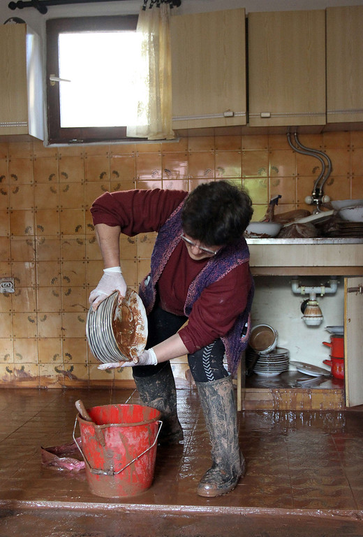 . A woman washes plates after floods hit her house in the town of Svilajnac, 120 kilometers south of Belgrade, on May 20, 2014. The Balkans were on alert Tuesday as swollen rivers were due to reach new peaks after days of devastating floods and landslides that have claimed at least 49 lives.  AFP PHOTO / SASA DJORDJEVIC/AFP/Getty Images