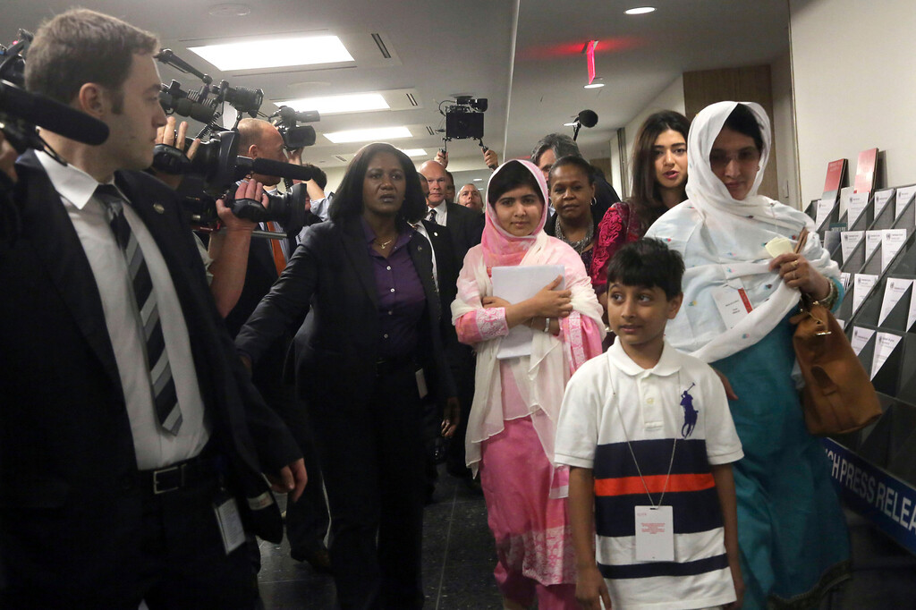 . Malala Yousafzai, center, is escorted past members of the media, Friday, July 12, 2013 at United Nations headquarters. Malala Yousafzai, the Pakistani teenager shot by the Taliban for promoting education for girls, will celebrated her 16th birthday on Friday addressing the United Nations. (AP Photo/Mary Altaffer)