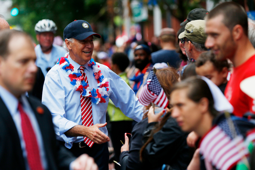 Description of . Vice President Joe Biden meets with spectators as he marches in an Independence Day parade, Friday, July 4, 2014, at Independence Hall in Philadelphia. (AP Photo/Matt Rourke)