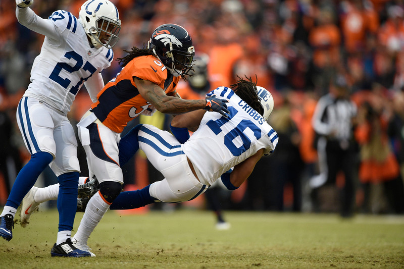 . Josh Cribbs (16) of the Indianapolis Colts is hit by Omar Bolden (31) of the Denver Broncos on a punt return in the first quarter. The Denver Broncos played the Indianapolis Colts in an AFC divisional playoff game at Sports Authority Field at Mile High in Denver on January 11, 2015. (Photo by John Leyba/The Denver Post)