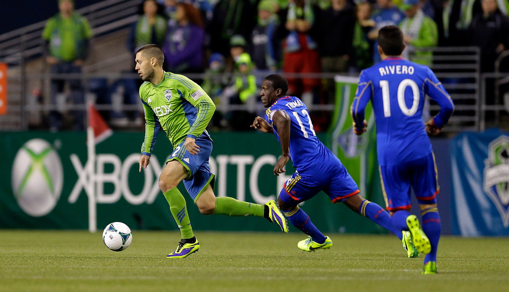 . Seattle Sounders\' Clint Dempsey, left, dribbles the ball ahead of Colorado Rapids\' Hendry Thomas, center, and Martin Rivero, right, in the first half of a knockout-round match in the MLS Cup soccer playoffs Wednesday, Oct. 30, 2013, in Seattle. (AP Photo/Ted S. Warren)