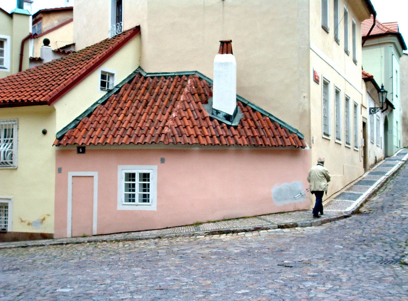 This is the smallest legal building parcel in Prague. Once a separate house, it's only door is blocked off and it is connected to the house on the left. The next photo follows the man walking up the lane.