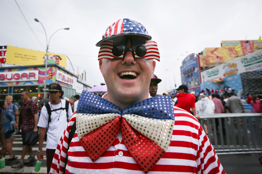 Description of . David Turner walks down Surf Avenue while wearing his American flag accessories after the Nathan's Famous Fourth of July International Hot Dog Eating contest at Coney Island, Friday, July 4, 2014, in New York. (AP Photo/John Minchillo)