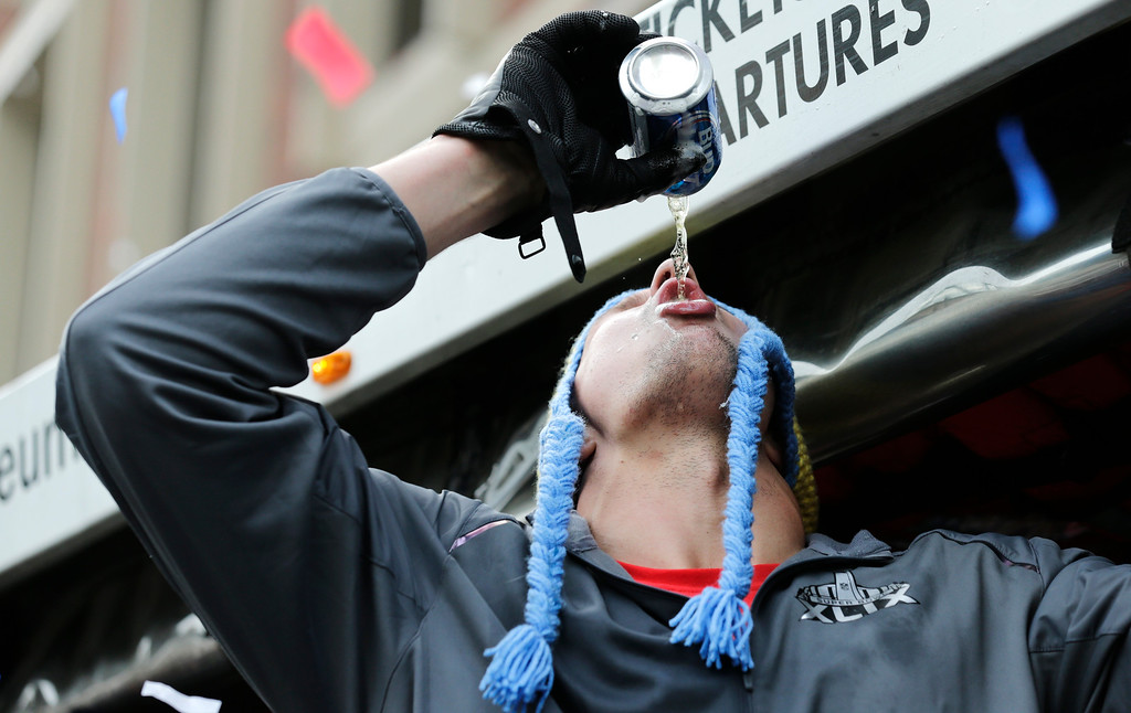 . New England Patriots tight end Rob Gronkowski chugs a beer, tossed to him by a fan, during a parade in Boston, Wednesday, Feb. 4, 2015, to honor the NFL football teams victory over the Seattle Seahawks in Super Bowl XLIX in Glendale, Ariz.  (AP Photo/Charles Krupa)