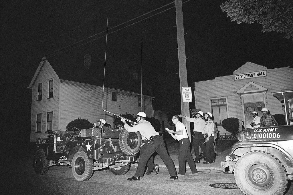 . Police and newsmen take cover as they investigate a report of a sniper firing in riot area of Cleveland as trouble continued into a fifth night, July 23, 1966. (AP Photo)