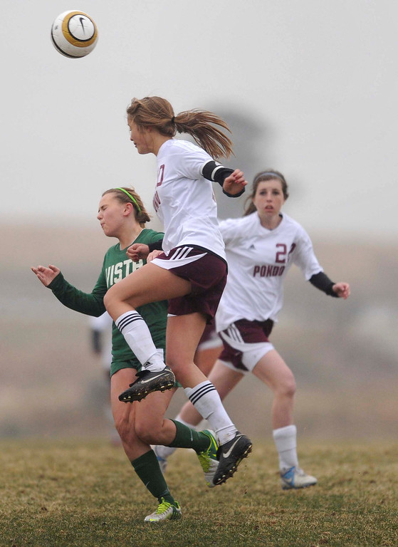 . Mustangs senior midfielder Kira Trombly (10) headed the ball past Golden Eagles forward Maddy Smith (12) in the second half. The Mountain Vista High School girl\'s soccer team defeated Ponderosa 6-0 Tuesday night, April 2, 2013.  Photo By Karl Gehring/The Denver Post)