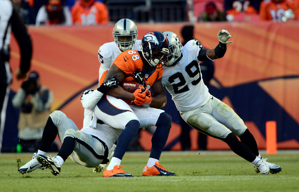 . DENVER, CO - DECEMBER 28: Demaryius Thomas (88) of the Denver Broncos catches the ball while getting wrapped up by Raiders in the third quarter.  The Denver Broncos played the Oakland Raiders at Sports Authority Field at Mile High in Denver on December, 28 2014. (Photo by Joe Amon/The Denver Post)