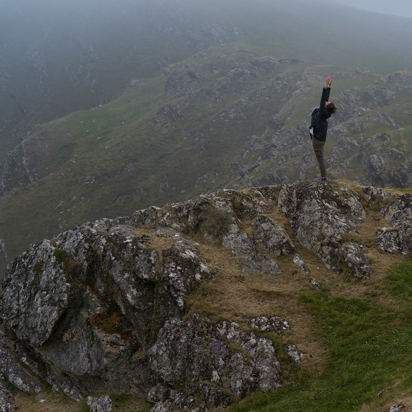 Woman with arms outstretched on the edge at Achill Island, County Mayo, Ireland