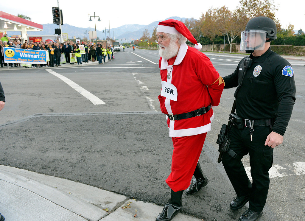 . Walmart protester Karl Hilgert, dressed as Santa Claus, is led away by an Ontario police officer after being arrested for failure to disperse after sitting down with 9 other protesters in the middle of the intersection at 5th and Mountain Avenues in Ontario Friday morning November 29, 2013. Over 100 protesters came to the Walmart on Mountain Avenue to protest against Walmart\'s wages and benefits.   (Will Lester/Inland Valley Daily Bulletin)
