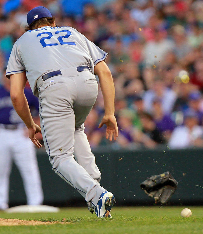 . Los Angeles Dodgers starting pitcher Clayton Kershaw (22) throws his glove at a bunt by Colorado Rockies\' Josh Rutledge during the sixth inning of a baseball game Tuesday, July 2, 2013 in Denver. Rutledge was out on the play. (AP Photo/Barry Gutierrez)
