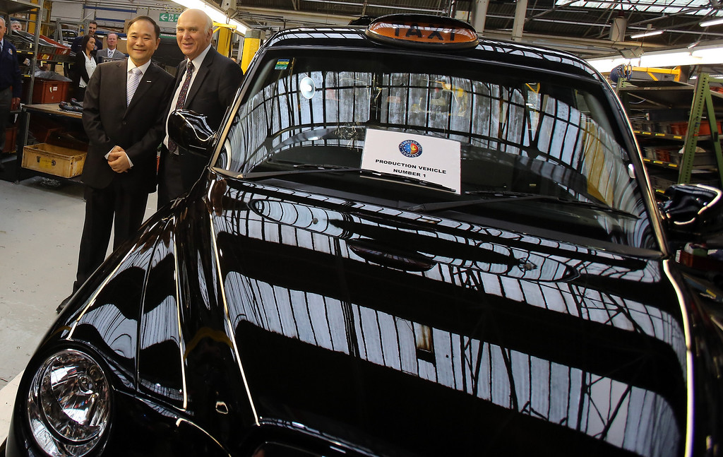 . Business Secretary, Vince Cable (2nd L) and Chairman Li Shufu, Chairman of  Zhejiang Geely Holding Group Co Ltd (L) officially restart production of TX4 (Euro 5) London Taxis inside the factory of The London Taxi Company on September 11, 2013 in Coventry, England. (Photo by Matt Cardy/Getty Images)