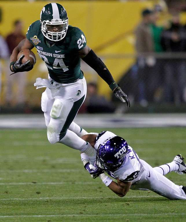 . Michigan State running back Le\'Veon Bell (24) is tripped up by TCU cornerback Kevin White (25) during the first half of the Buffalo Wild Wings Bowl NCAA college football game, Saturday, Dec. 29, 2012, in Tempe, Ariz. (AP Photo/Matt York)