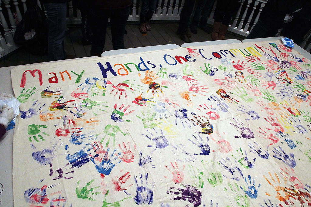 ". At a ceremony held at the Lunenburg town gazebo in support of Isacc Phillips, a Lunenburg eighth grader, they had a banner that read ""Many Hands one Community\"" that many but their handprints on.  SENTINEL & ENTERPRISE/ JOHN LOVE"