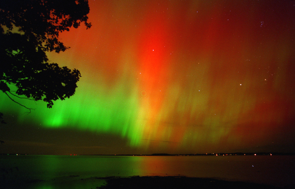 Description of . The northern lights, Aurora Borealis, dance over West Grand Traverse Bay, north of Traverse City, Mich., Sunday, Oct. 21, 2001. Caused by solar storms, the dancing lights lit up the northeast section of the sky all night, flashing colors as high as the zenith point, directly overhead. This is a 20-second exposure on 400 ASA film. (AP Photo/Traverse City Record-Eagle, John L. Russell)