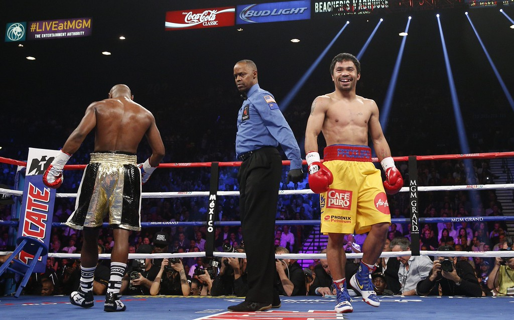 . Manny Pacquiao smiles at the end of round 1 against Floyd Mayweather Jr. in a welterweight unification bout on May 2, 2015 at the MGM Grand Garden Arena in Las Vegas, Nevada. AFP PHOTO / JOHN GURZINKSIJOHN GURZINSKI/AFP/Getty Images